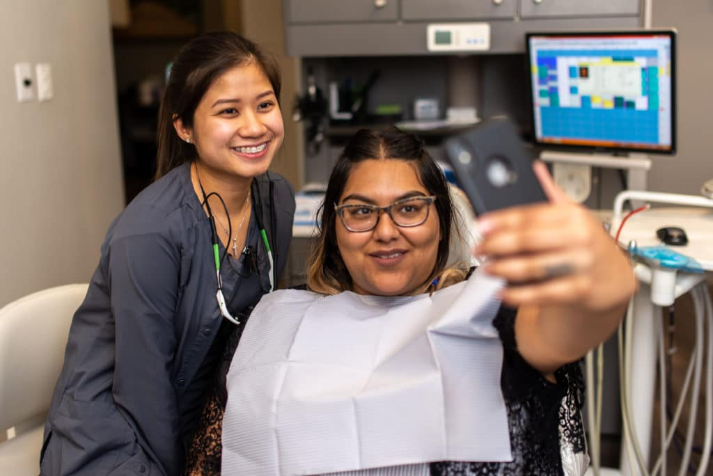 A patient taking a selfie with her dentist | dental career